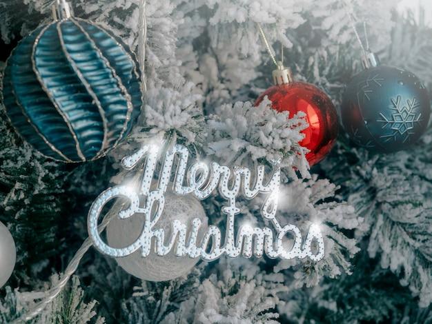 Weihnachten hintergrund. frohe weihnachten, feierwörter mit kugeldekoration auf tanne, die von weißem schnee bedeckt ist, nahaufnahme.