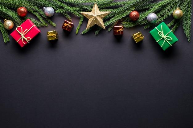 Weihnachten hintergrund. geschenke, tannenbaumaste, balldekorationen auf schwarzem hintergrund. flache lage, draufsicht, kopienraum.
