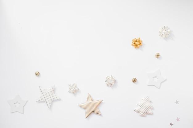 Weihnachten hintergrund. goldene sterne, glocken und bögen auf weißem hintergrund. flache lage, draufsicht, kopienraum