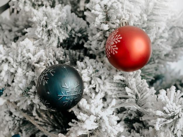 Weihnachten hintergrund. grüne und rote weihnachtskugeln dekoration auf tanne mit weißem schnee bedeckt, nahaufnahme.