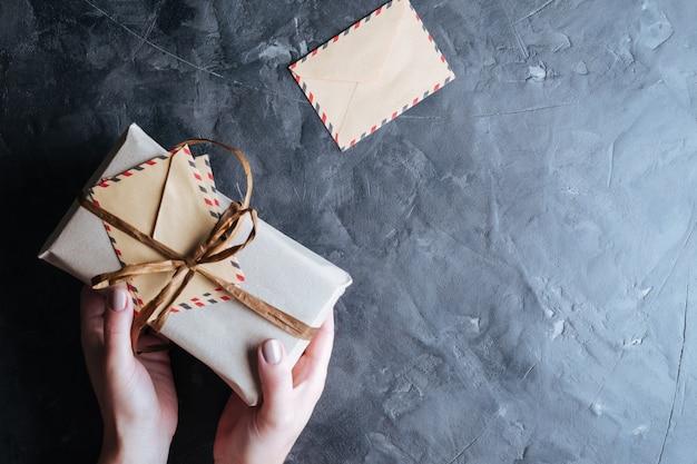 Weihnachten hintergrund. kästen mit geschenken in den händen auf dunkelheit