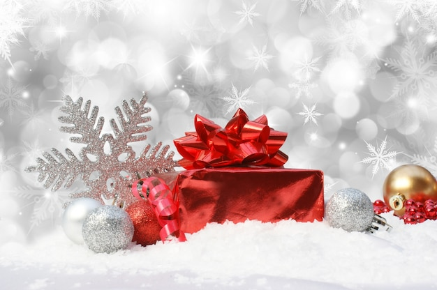 Weihnachten hintergrund mit kugeln und geschenk im schnee eingebettet
