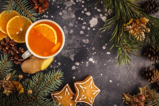 Weihnachten hintergrund sanddorntee mit ingwer und zitrusfrucht auf einem dunklen hintergrund.
