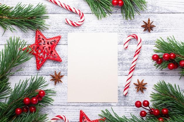 Weihnachten hintergrund. tannenzweige, zuckerstange und geschenke auf einem hellen hölzernen hintergrund.