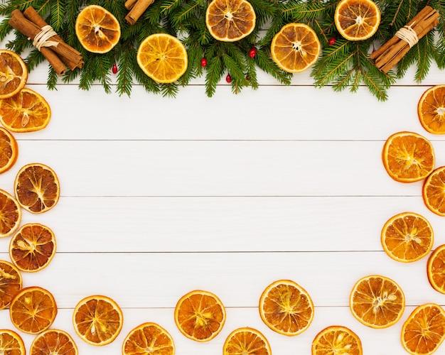 Weihnachten hintergrund. weihnachtstannenbaum, getrocknete orangen auf weißem hölzernem hintergrund mit kopienraum.