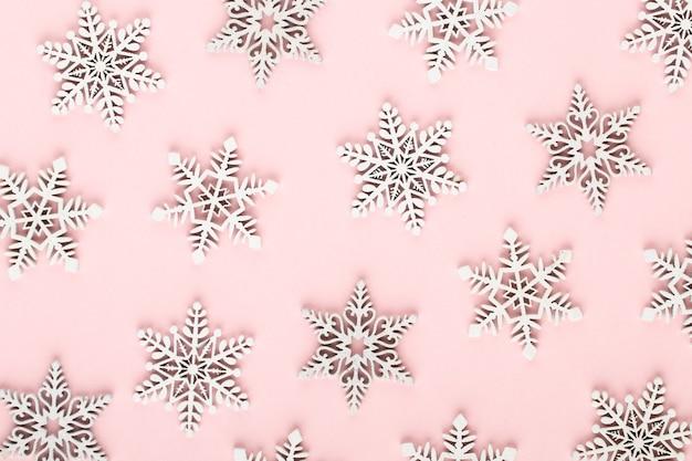 Weihnachten hintergrund. weiße schneedekorationen auf einem rosa hintergrund.