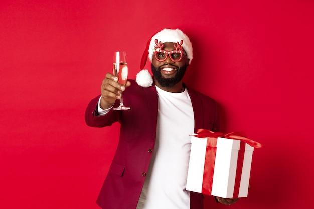 Weihnachten. hübscher afroamerikanermann in den partygläsern und in der weihnachtsmütze