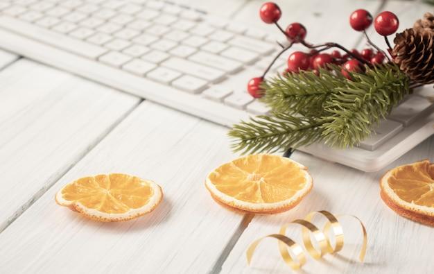 Weihnachten im büro, tastatur mit einem fichtenzweig und einem klumpen getrockneter orange.