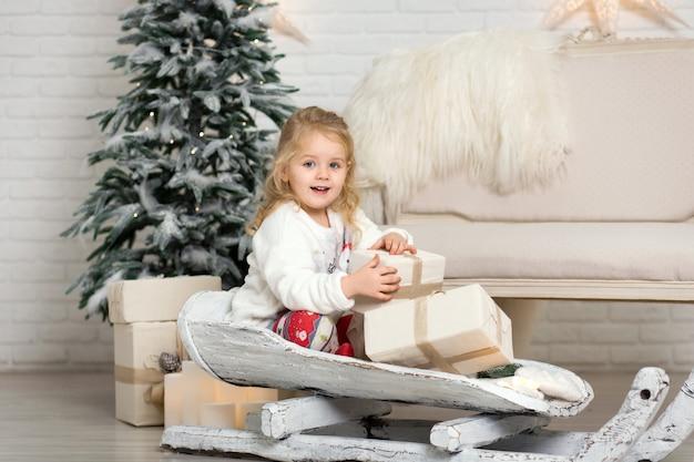 Weihnachten ist schon da. mädchen, das mit weihnachtsgeschenkbox rodelt. kleines nettes mädchen erhielt feriengeschenke. kindergriff-geschenkbox beim rodeln. weihnachten feiern. winteraktivität