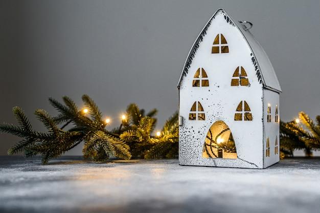 Weihnachten, kerzenständerhaus mit lichtern, tannenzweigen und weihnachtsspielwaren. frohes neues jahr.