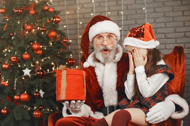 Weihnachten, kind und geschenke. der weihnachtsmann brachte dem kind geschenke. freudiges kleines mädchen, das den weihnachtsmann umarmt.