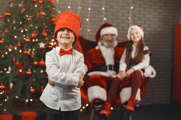 Weihnachten, kinder und geschenke. der weihnachtsmann brachte kindern geschenke. freudige kinder mit geschenken, die den weihnachtsmann umarmen.