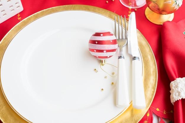 Weihnachten leerer weißer und goldener teller mit messer und gabel