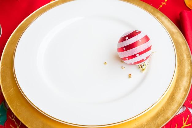 Weihnachten leerer weißer und goldener teller mit weihnachtskugel