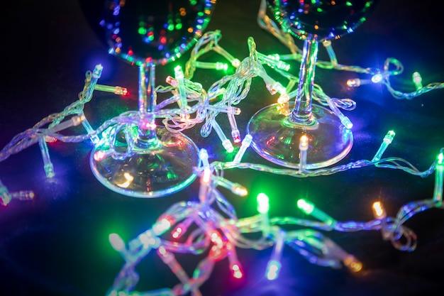 Weihnachten leuchtende bunte girlande spiegelt sich in glasgläsern auf dunklem hintergrund. neujahr feierlichkeiten....