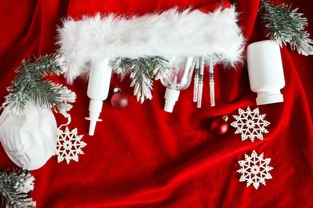 Weihnachten medizinische coronavirus flache lage, schützende gesichtsmaske, pillen, antiseptika, dekoration auf rotem hintergrund, neujahrsthema draufsicht, minimalismus, flaches layout, covid und frohes neues jahr konzept