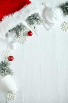 Weihnachten medizinische coronavirus flache lage, schützende gesichtsmaske, pillen, antiseptika, dekoration auf weißem hintergrund, neujahrsthema draufsicht, minimalismus, flaches layout, covid und frohes neues jahr konzept