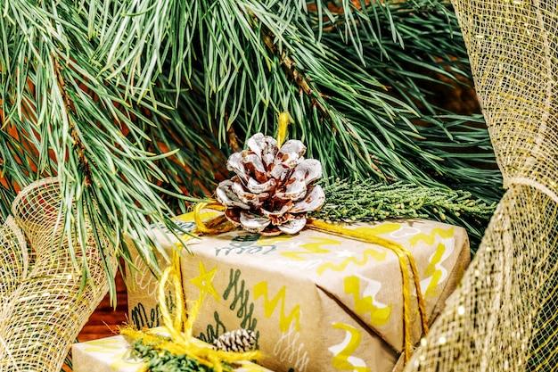 Weihnachten mit bastelgeschenkboxen goldene seilknäuel und tannenzapfen und zweig