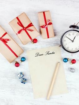 Weihnachten mit geschenkboxen, wecker, weihnachtsdekorationsbällen und blatt papier auf weißem holztisch