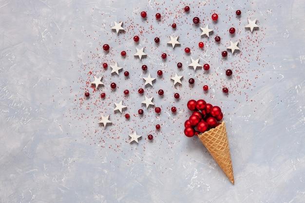 Weihnachten mit roten kugeln, moosbeere, sternen im waffelkegel besprüht mit rotem zucker.