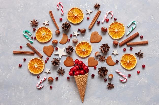 Weihnachten mit roten kugeln, zuckerstangen, plätzchen, gewürzen, trockenen orangenscheiben in der waffel.