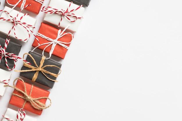 Weihnachten mit roten, schwarzen, weiß verpackten geschenkboxen mit band auf weiß