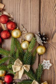 Weihnachten mit spielwaren des neuen jahres und tannenbaumast auf holztisch