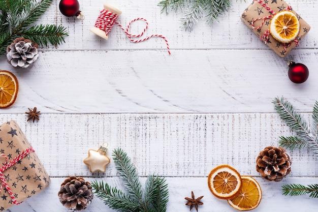 Weihnachten mit tannenzweigen, tannenzapfen, geschenkbox, getrockneten orangen, sternanis und beeren