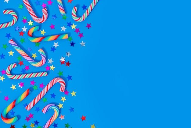 Weihnachten mit verschiedenen zuckerstangen- und sternkonfetti auf blau.
