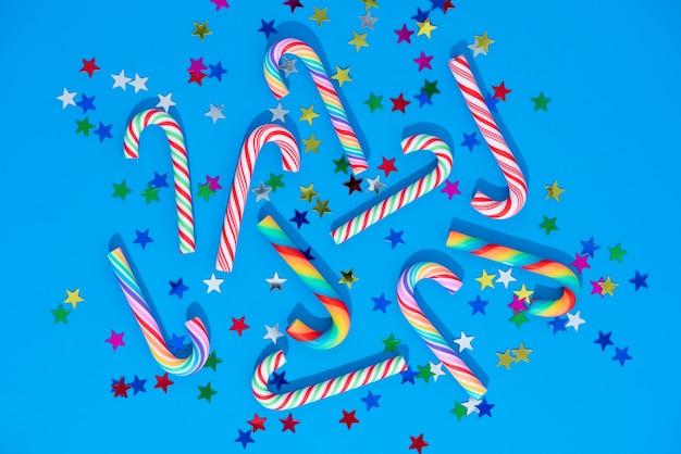 Weihnachten mit zuckerstangen und sternenkonfetti auf blau.