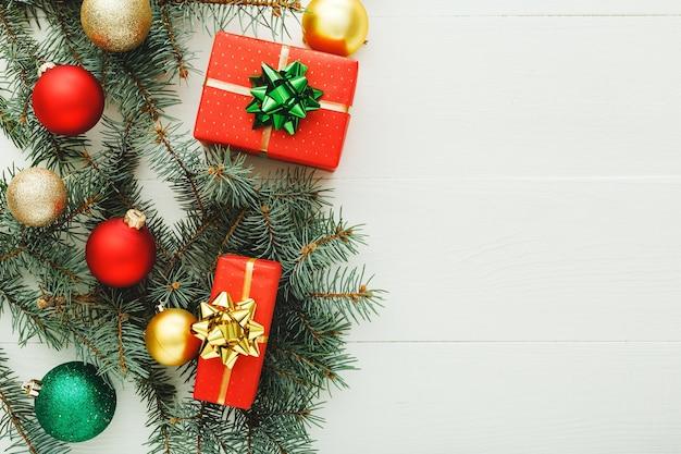 Weihnachten neujahr 2020 feiertagsfeier musterzusammensetzung aus roten geschenkboxen, tannenzweigen, kugeln auf weißem holzhintergrund. konzept weihnachtszeit, winter. flache lage, ansicht von oben, kopienraum