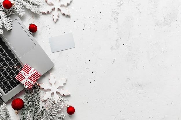 Weihnachten, neujahr einkaufen graue betonflachlage. laptop-computer, leere leere kreditkarte, draufsicht der roten weißbuchgeschenkboxen. tannenzweig, spielzeugbälle, sterne. leerraum auf foto kopieren