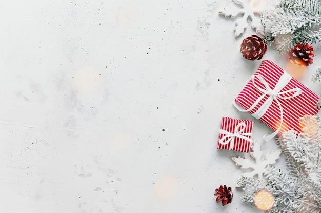 Weihnachten, neujahr graue betonflachlage. draufsicht der rot-weiß gestreiften geschenkboxen. geschenkband und verpackungspapier. weihnachtsbaumtanne, zapfen, spielzeugbälle, holzstern. leerraum auf foto kopieren