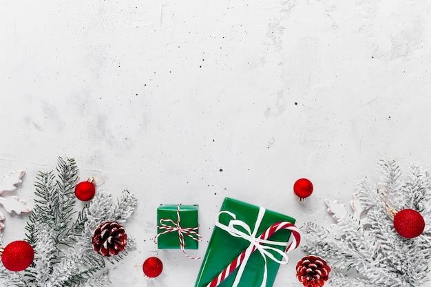 Weihnachten, neujahr grauer beton flach mit grün-weißer geschenkbox-draufsicht. geschenkband und verpackungspapier. weihnachtsbaumtanne, zapfen, spielzeug, roter bonbonstäbchen, textbereich kopieren