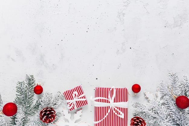 Weihnachten, neujahr grauer beton flach mit rot-weißer geschenkbox-draufsicht. geschenkband und verpackungspapier. weihnachtsbaumtanne, zapfen, spielzeug. kopieren sie den leerraum-textbereich auf ein hochwertiges foto
