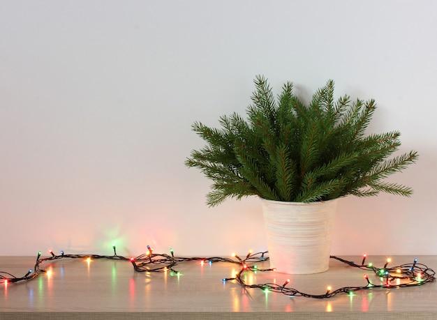 Weihnachten neujahr hintergrund grüne zweige weihnachtsbäume und elektrische girlanden auf dem festlichen hintergrund des tisches