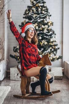 Weihnachten, neujahr. hübsche frau in hemd und socken haben spaß beim reiten auf dem hölzernen schaukelpferdespielzeug