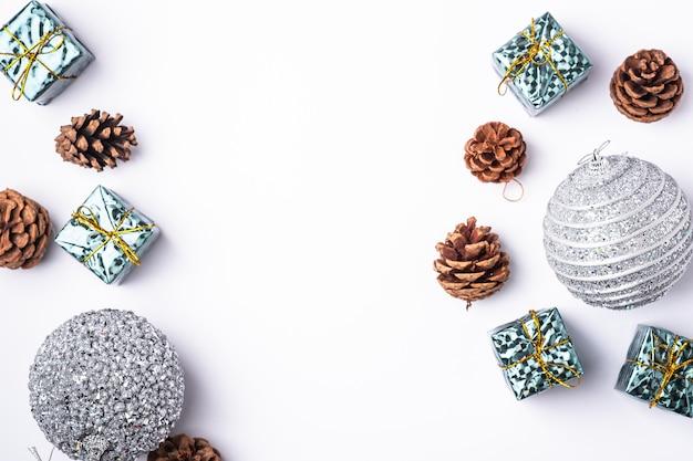 Weihnachten neujahr komposition. geschenke, tannenzapfen, silberne kugeldekorationen auf weißem hintergrund. winterferienkonzept. flache lage, draufsicht, kopierraum