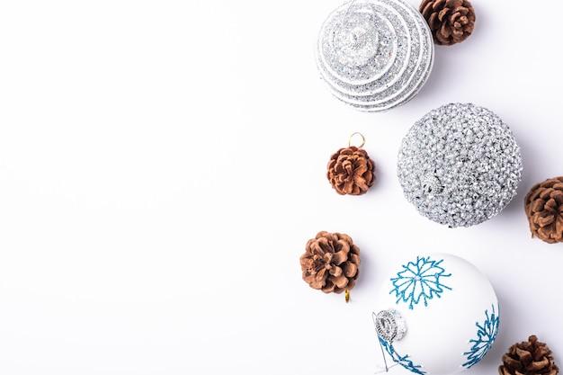 Weihnachten neujahr komposition. geschenke, tannenzapfen, silberne kugeldekorationen auf weißem hintergrund. winterferienkonzept. kopierbereich der draufsicht