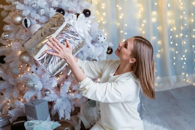 Weihnachten neujahr schöne frau in hellem kleid und socken sitzt auf dem boden mit einer weihnachtsgeschenkbox ...