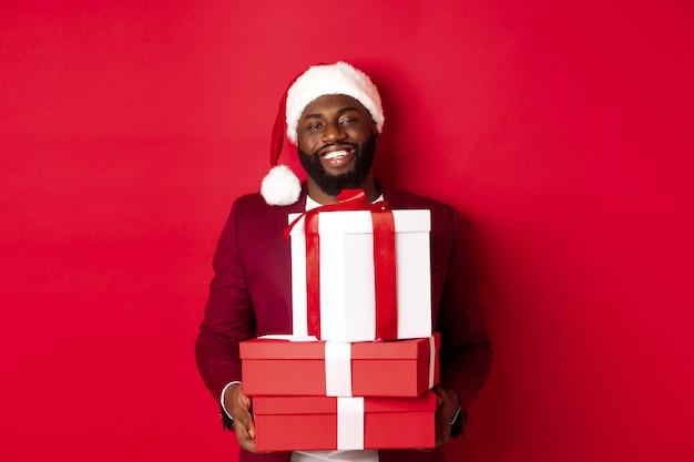 Weihnachten, neujahr und einkaufskonzept. glücklicher schwarzer mann in weihnachtsmütze und blazer, der weihnachtsgeschenke hält, geschenke bringt und lächelt, vor rotem hintergrund stehend.