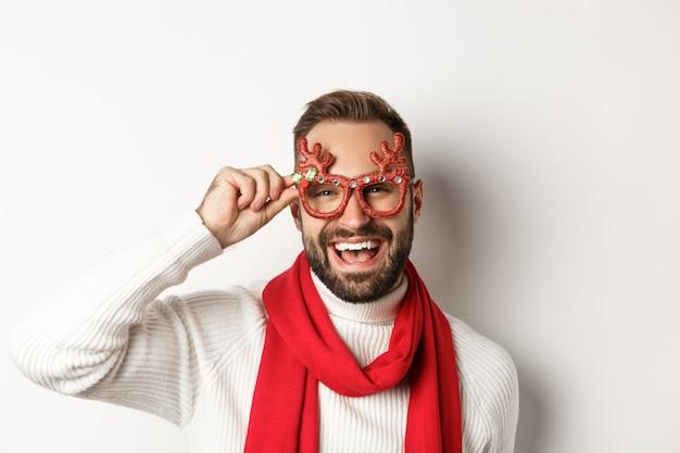 Weihnachten, neujahr und feierkonzept. fröhlicher bärtiger kerl in partybrille, der die winterferien lacht und genießt, weißer hintergrund