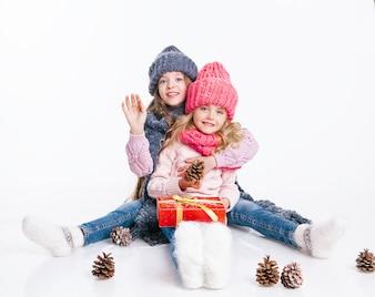 Weihnachten. Neujahr. Zwei kleine Schwestern, die Geschenk in der Winterkleidung anhalten. Rosa, graue Hüte