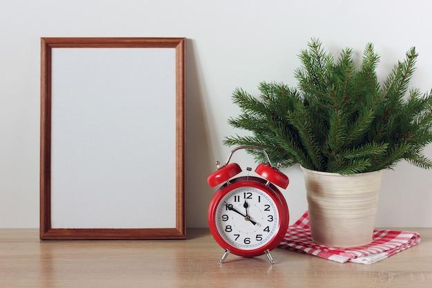 Weihnachten neujahrsmodell mit einem leeren rahmen auf dem tisch festliche kulisse mit einem weihnachtsbaum und einem wecker silvester heiligabend