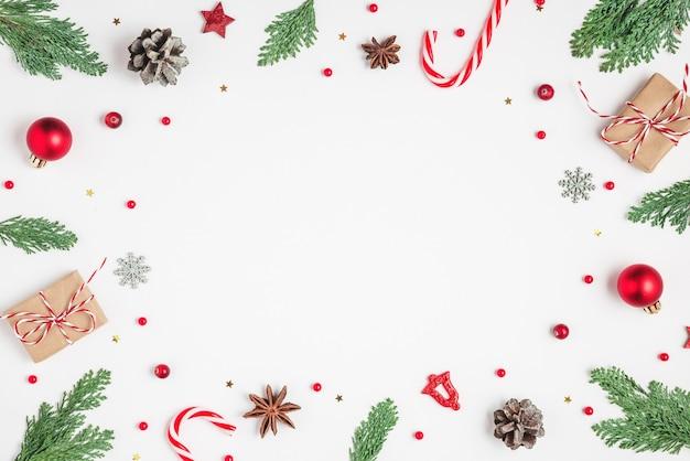 Weihnachten oder guten rutsch ins neue jahr-zusammensetzung. rahmen aus tannenzweigen, weihnachtsdekorationen, süßigkeiten und geschenkboxen auf weißem hintergrund. flach liegen. draufsicht mit kopienraum