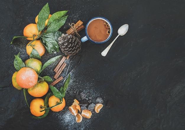 Weihnachten oder neujahr rahmen. frische mandarinen mit blättern, zimtstangen, vanille, tannenzapfen und becher heißer schokolade über dunklem stein, draufsicht
