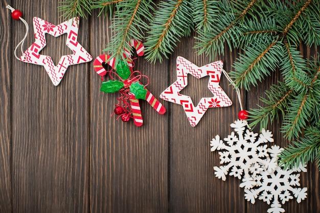 Weihnachten oder neujahr. tannenzweige, weihnachtsbaumspielzeug, sterne, schneeflocken und zapfen auf dunkelbraunem holz.