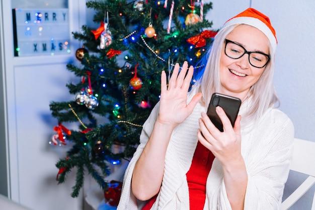 Weihnachten online familie glückwünsche. lächelndes mädchen zu hause mit laptop