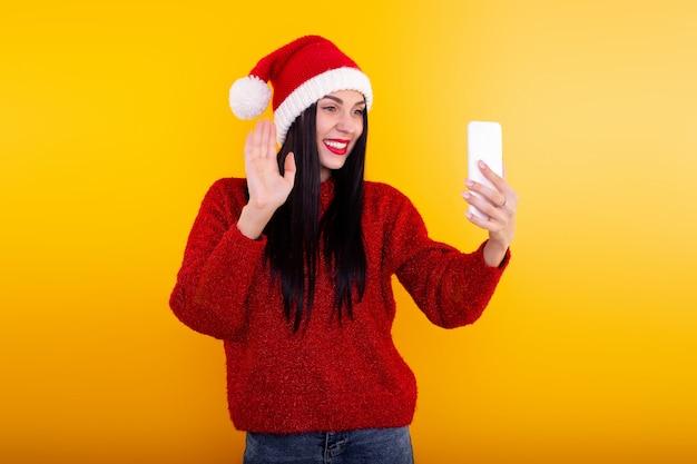 Weihnachten online glückwunsch. frau in der weihnachtsmütze mit mobilem tablet für videoanruffreunde und eltern.