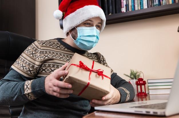 Weihnachten online glückwunsch. junger mann im weihnachtsmannhut und in der gesichtsmaske gibt ein geschenk und spricht unter verwendung des laptops für videoanruffreunde und -kinder. weihnachten während des coronavirus.